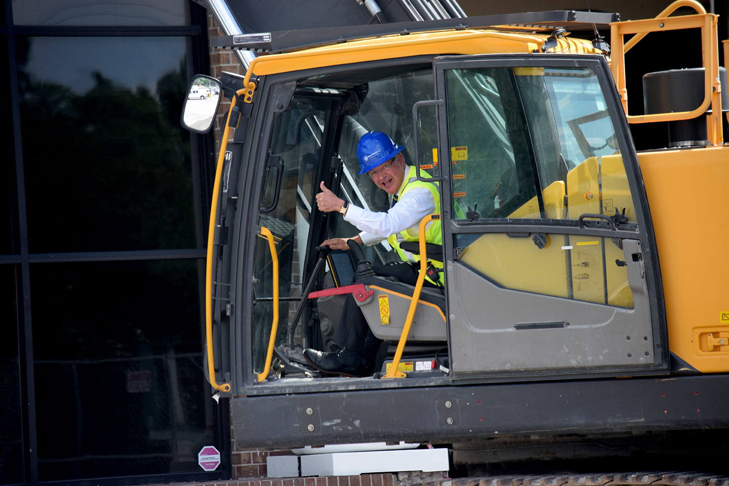 "Mayor Tecklenburg gives the crowd a thumbs-up before landing the excavator's initial blow on the former Piggly Wiggly. ""I'm really looking forward to (this),"" he said. (Photo/Patrick Hoff)"