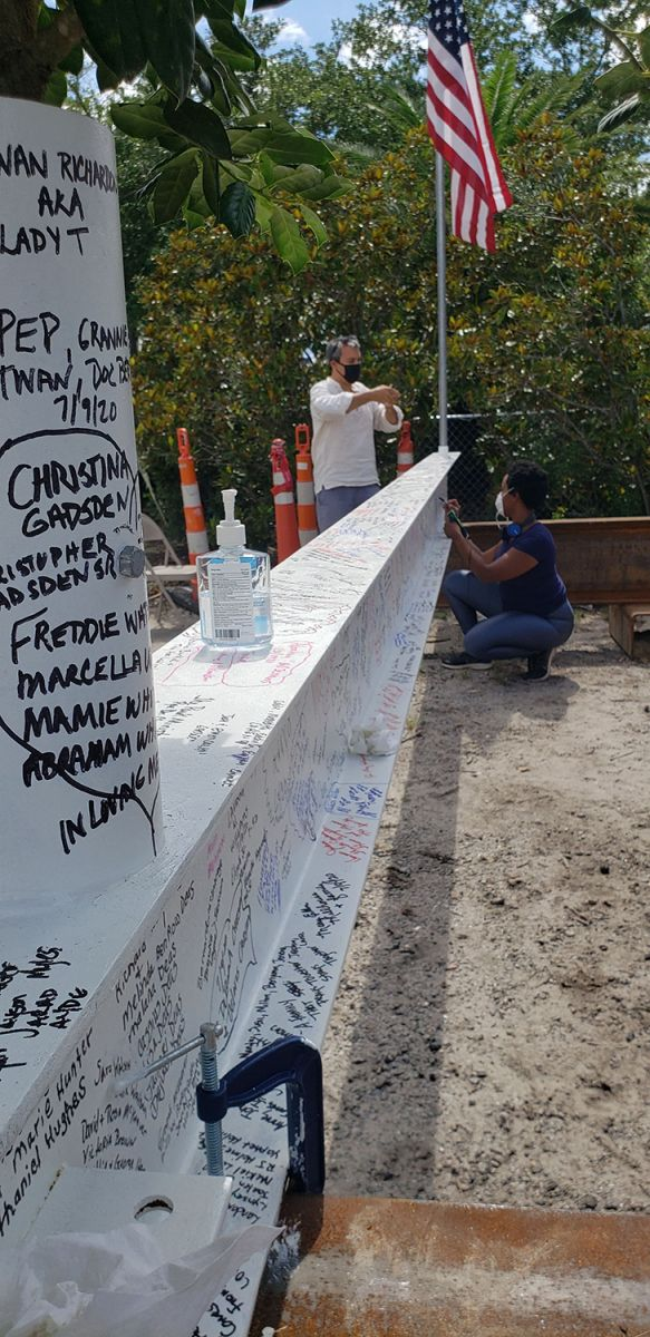 Signatures fill the topping-out beam, which has an American flag on one end and a small tree on the other. (Photo/Beverly Barfield)