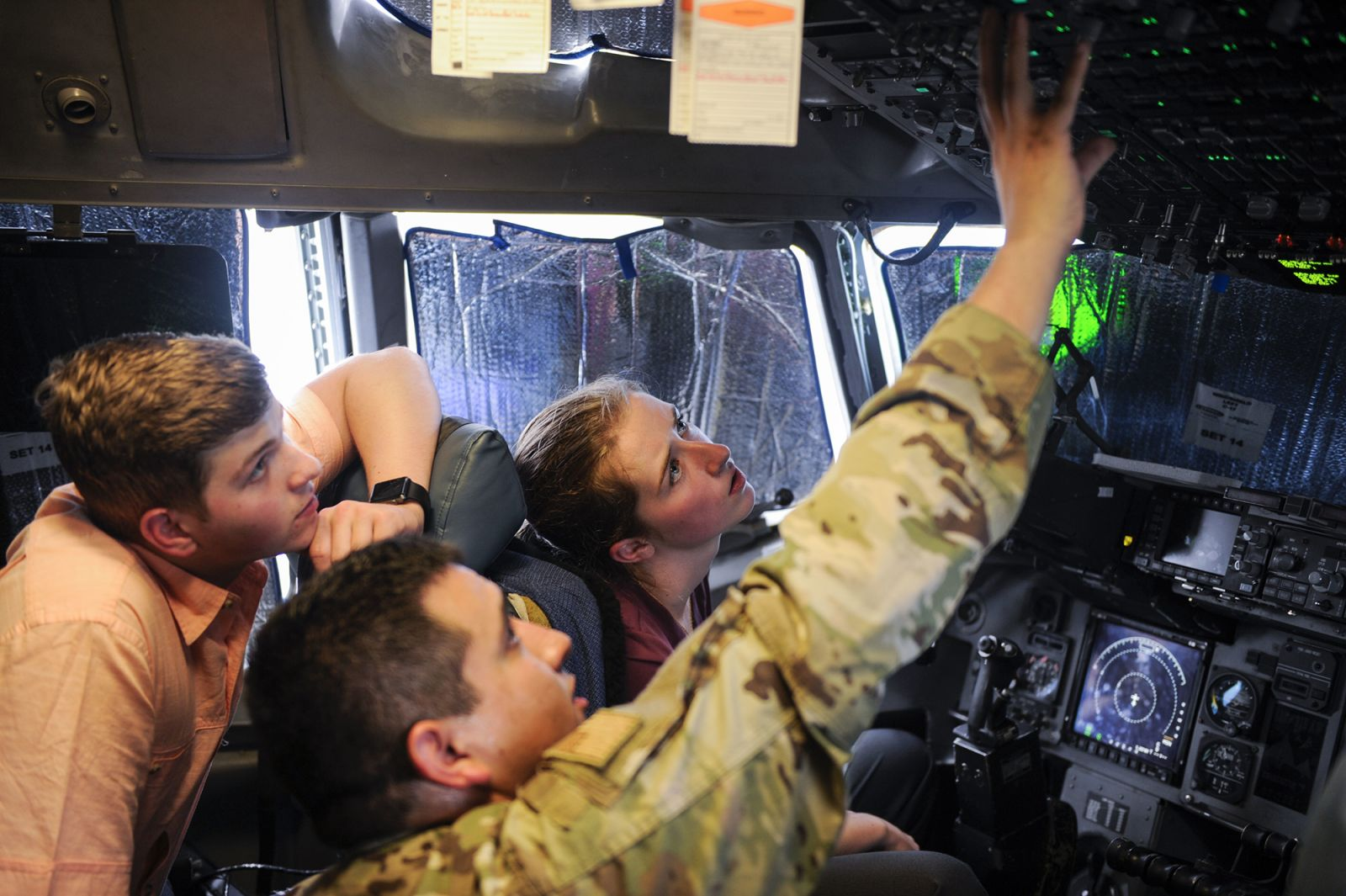 Senior Airman Ulises Zamora (center), a crew chief assigned to the 437th Aircraft Maintenance Squadron, explains some of the controls used on a C-17 Globemaster III to interns Aleric Stell (left) and Emma McBride. (Photo/Senior Airman Thomas T. Charlton for the Air Force)