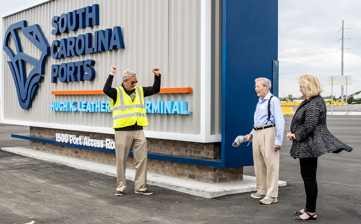 S.C. Ports Authority President and CEO Jim Newsome celebrates with Hugh K. Leatherman and Jean Leatherman as the senator breaks a bottle of champagne across the sign of the new namesake terminal. (Photo/Kim McManus)