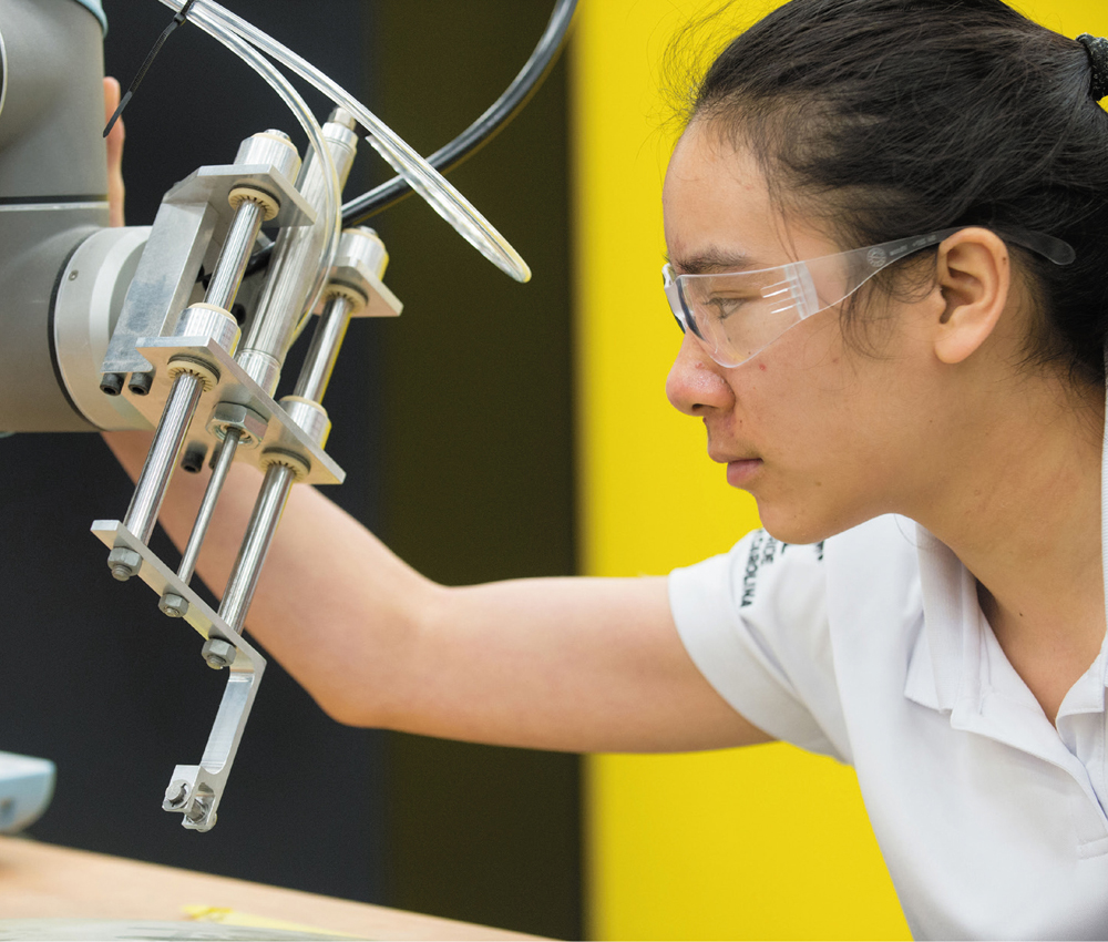 BR&T-SC teammate Rachel Chow works with a collaborative robot to test its joint sensitivity.