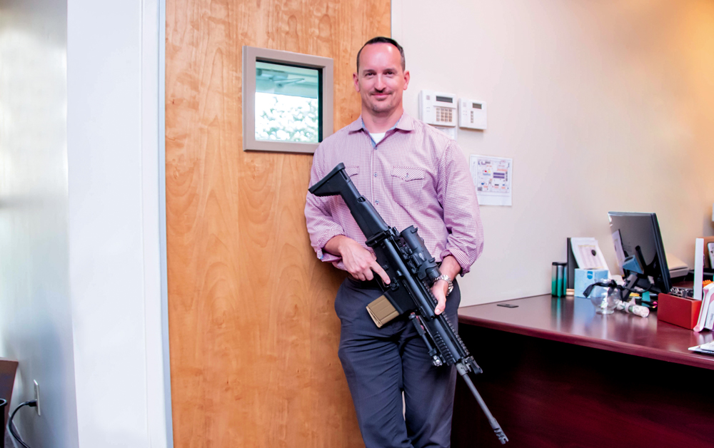 Retired Special Forces soldier Kirk Ferguson stands in front of one of his company's ballistic doors with a 7.62-mm SCAR-Heavy rifle, an example of the type of weapon the door is designed to withstand.