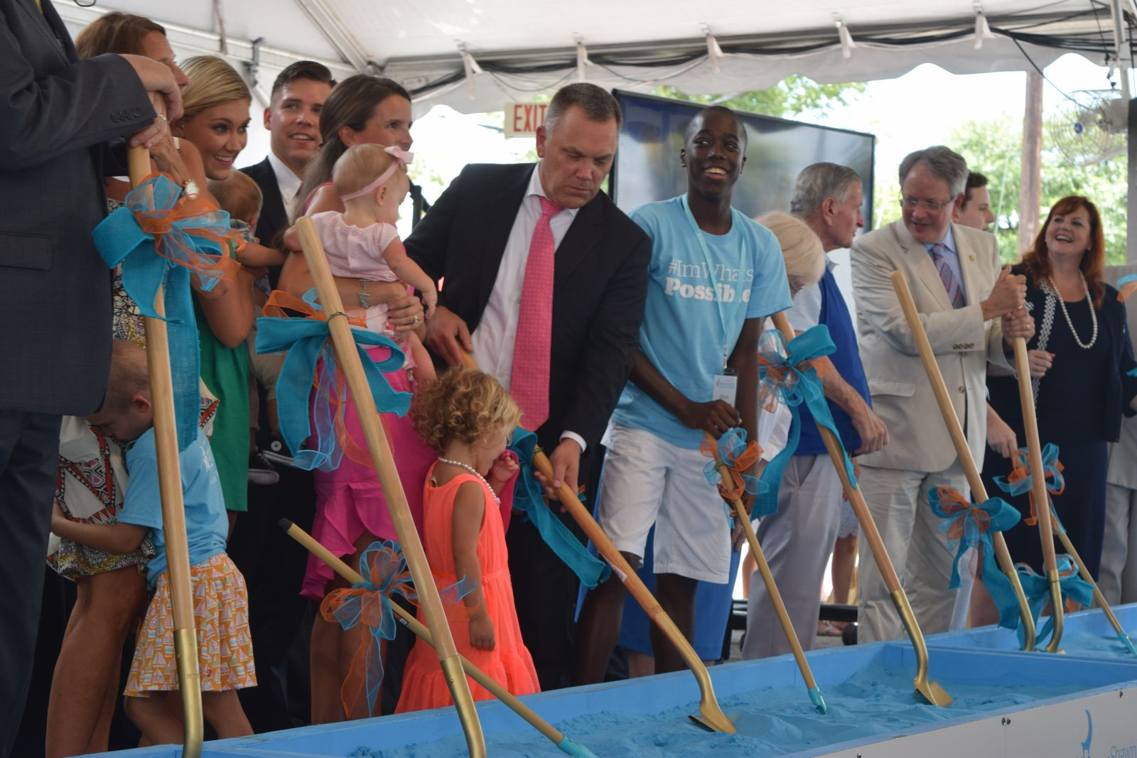 Shawn Jenkins (center in pink tie) helps break ground Friday on the new children's hospital that will bear his name. (Photo/Ashley Heffernan)