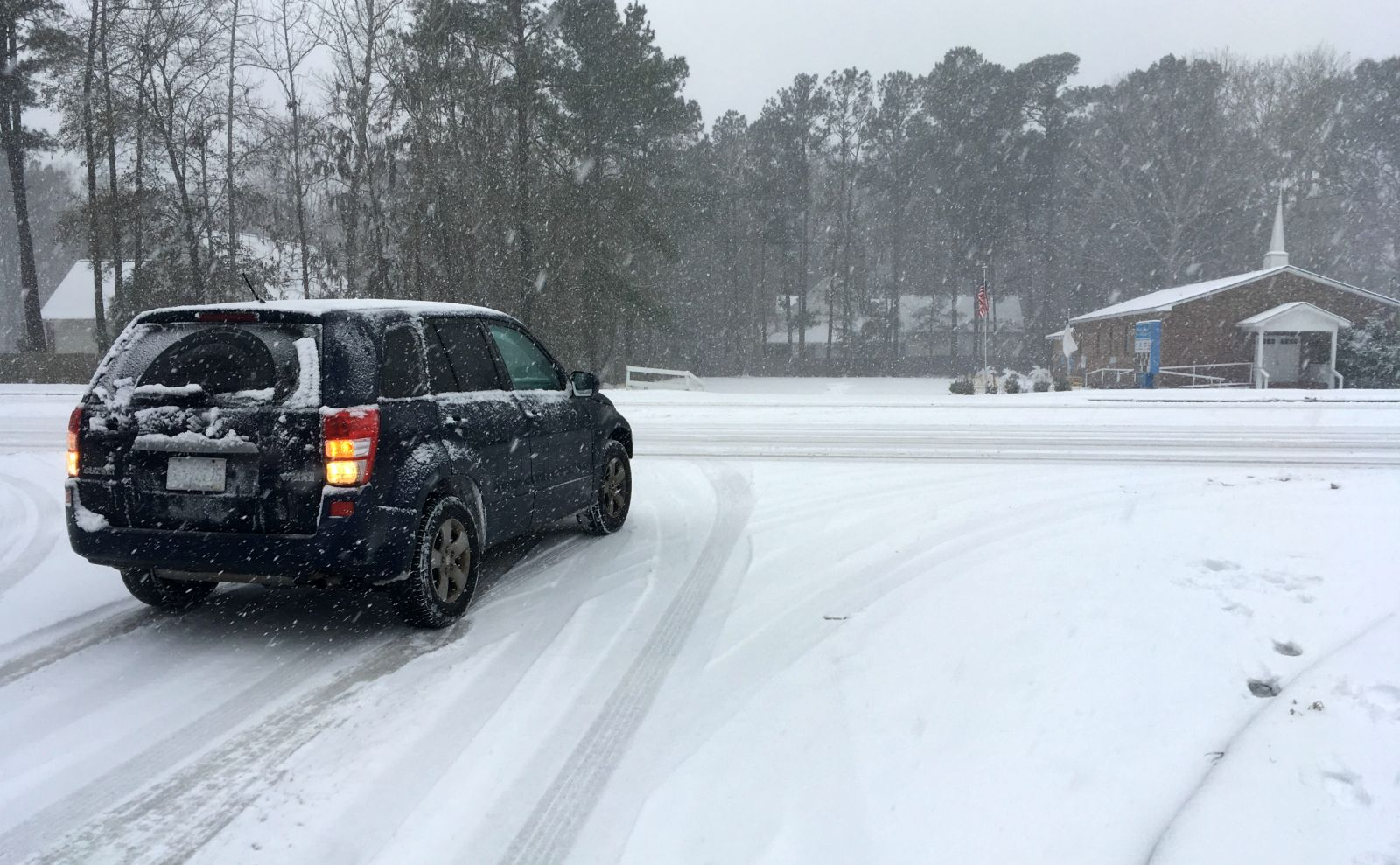 A vehicle tries to pull out onto Bacons Bridge Road in Summerville this afternoon. The typically busy four-lane road was mostly empty as snow continued to fall around the region. (Photo/Andy Owens)
